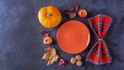 Autumn harvest festival and thanksgiving day table setting. Fallen leaves, pumpkin, apples, nuts, empty plate and checkered napkin. Thanksgiving rustic still life, mock up, banner