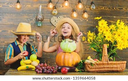 Autumn harvest festival. Children play vegetables pumpkin cabbage. Kids girl boy wear hat celebrate harvest festival rustic style. Celebrate fall traditions. Elementary school fall festival idea.