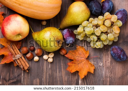 Autumn harvest. Pears, apple, grapes and yellow leaves on the wooden table