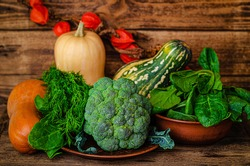 Autumn harvest still life. Rural vegetables background. Pumpkins,broccoli, spinach and dill