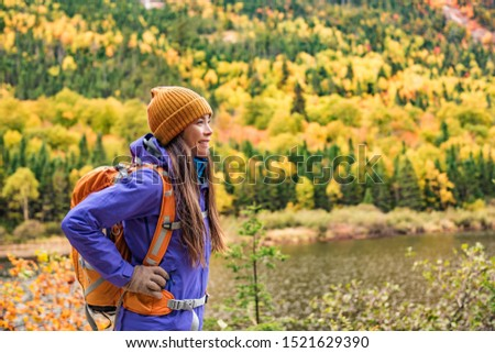 Autumn hiker girl outdoor in nature forest lake backpacking for camping travel trip. Happy Asian woman hiking outdoors with bag and hat, cold outerwear gear. #1521629390