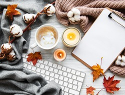 Autumn home cozy composition. Women's home office desk. Dried autumn leaves, cup of coffee, keyboard, clipboard, cotton flowers on white wooden background. Flat lay, top view, copy space