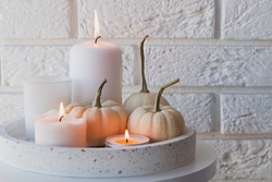 Autumn home decor with white pumpkins and burning candles. Cozy fall composition