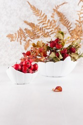 Autumn home decoration with red dried leaves rosehip, fern leaf, ripe berries hawthorn in bowl on white wood table, vertical.