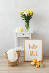 Autumn home interior decor. Bedside table, frame with text HELLO FALL, vase with white and yellow chrysanthemums flowers, wicker straw bag, squashes (bush pumpkins) Cozy modern stylish room, gray wall