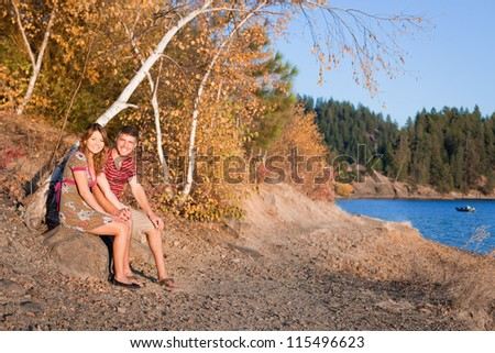 autumn in idaho, young couple sitting by the lake watching the sunset