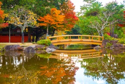 Autumn in Japan. Bridge over the river in Nara Park. Autumn in Nara. Autumn landscape with a bridge. Panorama of the Japanese Nara Park. Natural attractions of Japan. A well-known place for recreation