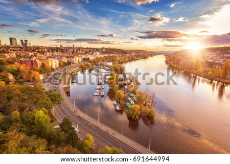 Autumn in Prague, golden sunset from popular view point, Vyshehrad. Aerial view to the residential area, Vltava river with islands and beautiful blue cloudy sky and sun, Czech Republic