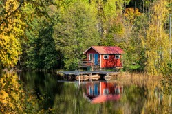 Autumn in Sweden - traditional red little cabin at a lake