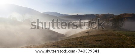 Autumn in the mountains with fog and colorful trees - rural panoramic landscape #740399341