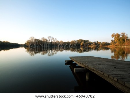 Autumn lake scene with wooden dock - stock photo
