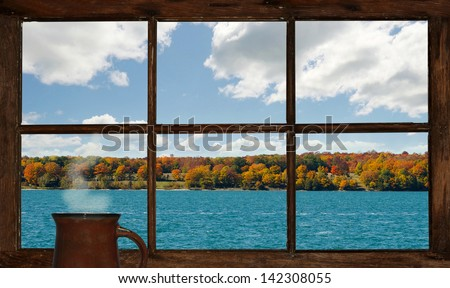 Autumn lakefront view with a cup of steaming coffee, as seen through the cottage window. Part of a series.