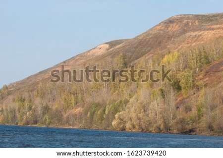 Autumn landscape, dark blue water, last warm days, river, trees, windy weather, yellow-red autumn leaves