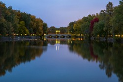 Autumn landscape. Evening time, colorful trees, slowly river. Mirror water  and old stone bridge with lights . Guelph, Ontario, Canada