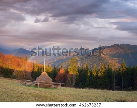 Autumn landscape in a mountain village. Haystack on the meadow. Rainbow over the hills. Collage of two frames. Art processing photos