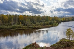 Autumn landscape of a forest river with a cloudy sky. Nature background, riverbank. Kosva River, Perm region, Ural, Russia.