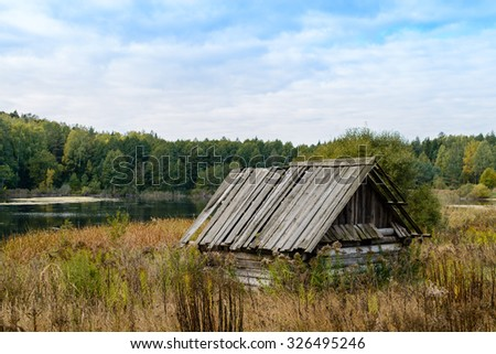 Autumn landscape. Old abandoned village on the empty field. Deteriorated typical ancient wooden abandoned house at village. Destroyed abandoned house standing in the forest. Belarus, Europe #326495246