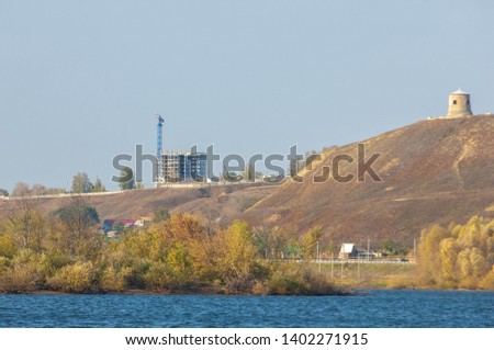 Autumn landscape, river, windy weather, dark blue water, yellow-red autumn leaves on trees, last warm days