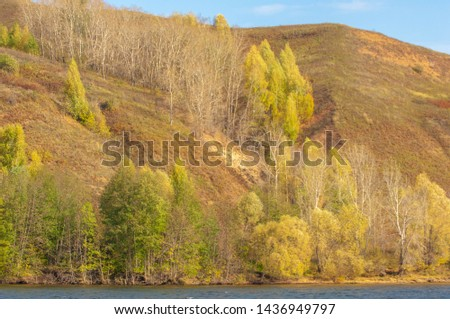 Autumn landscape, river, windy weather, dark blue water, yellow-red autumn leaves on trees, last warm days #1436949797