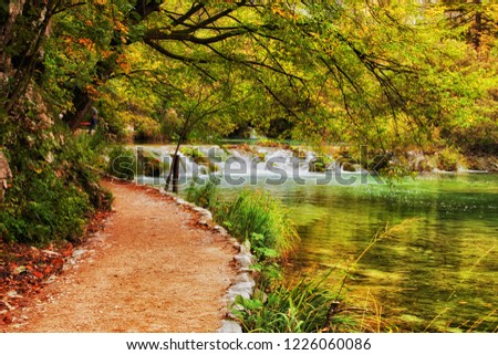 Autumn landscape with path along the lake with water cascade in Plitvice Lakes National Park, Croatia, Europe. #1226060086