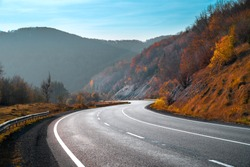 Autumn landscape with road in mountains. Travel background. Highway in mountains under clear blue sky.