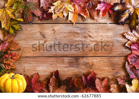 Autumn leaf frame with pumpkin over wooden ground - stock photo