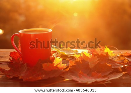 Autumn leaves and hot steaming cup of coffee. Wooden table against golden sunset or sunrise light background. Fall season, leisure time and coffee break concept.