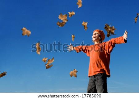 autumn leaves falling on boy