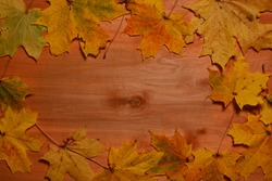 autumn leaves on a wooden background with place for text in the middle. thanksgiving and greeting card concept. copy space.