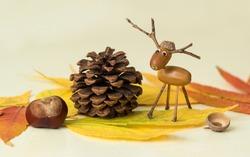 Autumn leaves, pine cone, horse chestnut and acorn deer figure.