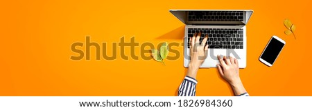 Autumn leaves with person using a laptop computer from above