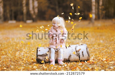 Autumn lifestyle photo child throws up the leaves and having fun, positive little girl