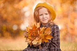 Autumn. Little girl is posing in beautiful autumn park with a bouquet of autumn leaves in her hands. Retro style. Children's fashion.