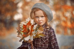Autumn. Little girl walks through a beautiful autumn park and collects leaves fallen from trees. Retro style. Children's fashion.