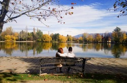 Autumn love, young loving couple sitting on a bench in front of the lake of Puigcerda, Spain