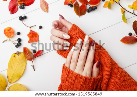 Autumn manicure. Beautyful nails design with autumn leaves. Top view. cozy autumn image. Cozy nails design. autumn leaves. Manicured woman's hands in warm wool turquoise sweater on wooden background