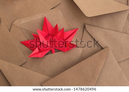 Autumn maple leaf on a background of envelopes. Origami from colored paper. The concept of incoming messages, alerts, discounts, sales. Autumn bright background, postcard  #1478620496