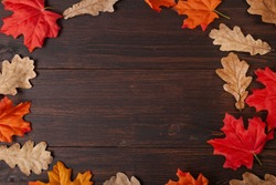 Autumn maple leaves oak on brown wooden table. Board from autumn leaves with empty space for text. Fall background , Top view
