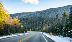 Autumn maples and winter snow-covered winding road with first snow dusted trees on the mountains in Vermont invite tourists and travelers to visit the meeting point of the two seasons in New England
