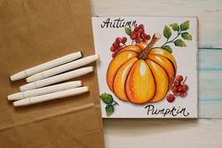 Autumn mood backstage with sketch with markers. Pumpkin with red berries