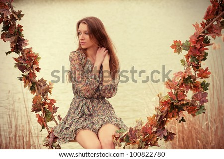 Autumn mood. Beautiful woman sitting on the swing decorated with garland of autumn leaves