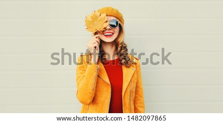 Autumn mood! happy smiling woman holding in her hands yellow maple leaves covering her eye over gray wall background