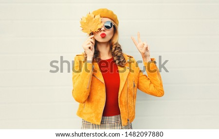 Autumn mood! woman holding in her hands yellow maple leaves covering her eyes over gray wall background