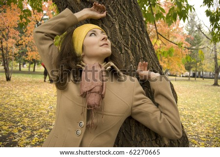 Autumn mood. Young attractive cheerful woman posing at park