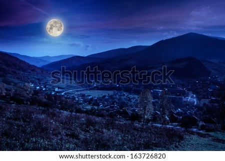 autumn moon landscape. village on the hillside. forest on the mountain covered with red and yellow leaves.