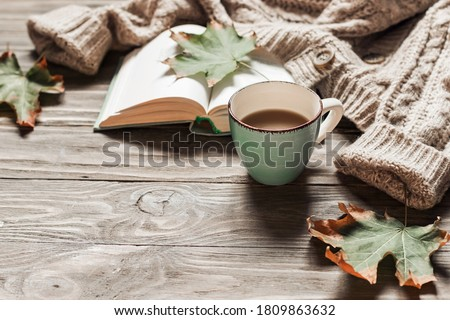 Autumn morning coffee. A cup of coffee on a wooden table and a warm sweater on a background of autumn leaves. Still life concept. Copy space. Foto stock ©