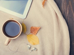 Autumn morning. Cup of coffee, tablet, earphones and warm blanket, top view. Toned photo.