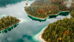 Autumn morning in the Bavarian mountains, Germany. Alps landscape with lake, clouds, island, spruce forest and turquoise water. View from above. Aerial drone outdoor photo.