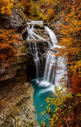 Autumn mountain waterfall vertical view. Mountain forest waterfall in autumn. Autumn waterfall in autumnal mountain forest. Autumn waterfall in mountains