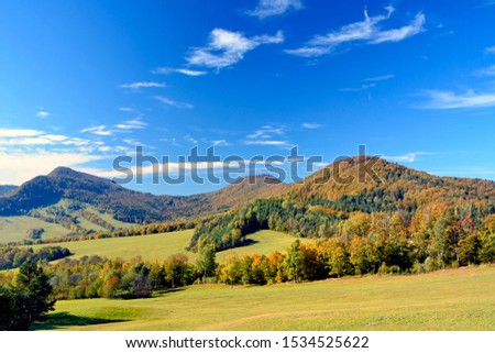 Autumn mountains landscape. Trees on a  slope  with dry grass and wooded mountains under blue sky with white clouds, Low Beskids (Beskid Niski) Zdjęcia stock ©